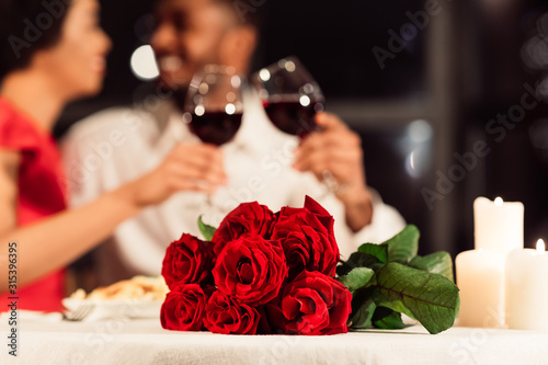 Photo Roses Lying On Table, Unrecognizable Spouses Drinking Wine In Restaurant