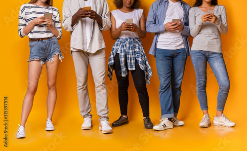 Photo Teenaged mixed race group of friends using smartphones, cropped