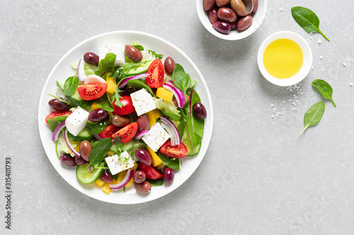 Greek salad with greens, olives and feta chesse on a white plate, top view Wallpaper Mural