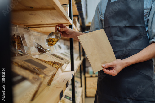 Mixed race male worker shop assistant filling paper bag with oat granola in bulk products in dispensers and food available at zero waste shop Canvas