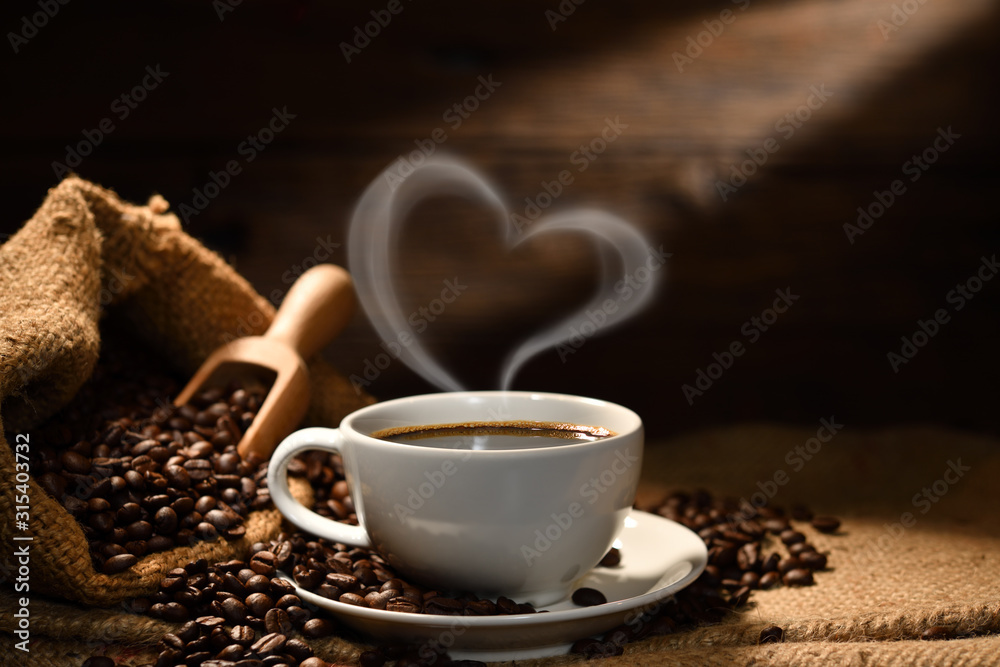 Fototapeta Cup of coffee with heart shape smoke and coffee beans on burlap sack on old wooden background