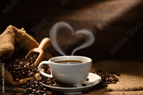 Obraz Cup of coffee with heart shape smoke and coffee beans on burlap sack on old wooden background - fototapety do salonu