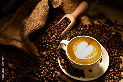 Cup of coffee latte with heart shape and coffee beans on old wooden background Fototapete