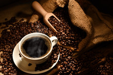 Cup Of Coffee With Smoke And Coffee Beans On Burlap Sack