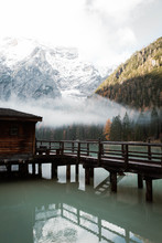 Wooden House On Stilts And Boats On Nebulous Lake With Reflection Of Powerful Dolomites Mountains At Italy