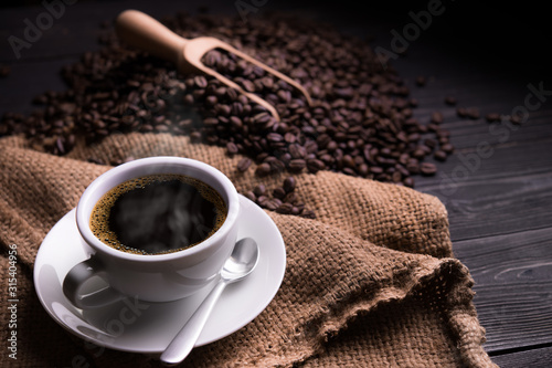 Fototapeta Cup of coffee with smoke and coffee beans on old wooden background obraz