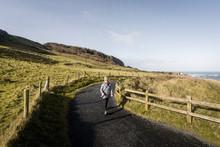 Woman Walking On Narrow Rural ...
