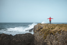 Back View Of Faceless Free Female In Warm Outfit On Cliff Top Enjoying Stormy Raging Surf With Spread Arms In Ballintoy