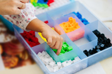 Hands Over Blue Transparent Box Organizer With Small Colorful Plastic Mosaic Pieces For Children Educational Board Game With Empty Section
