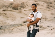 Cheerful Bearded African American Man In White T Shirt And Jeans Holding Newborn In Baby Carrier While Strolling On Nature
