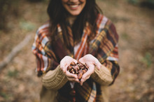 From Above Blurred Female Smiling And Demonstrating Handful Of Chestnuts While Spending Time In Forest