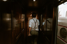 Back View Of Anonymous Man In Vintage Clothes Pulling Luggage And Walking In Hallway Of Old Train