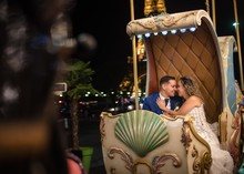 Happily Married Young Man In Blue Suit And Woman In Wedding Dress Looking At Each Other While Taking Amusement Rides In An Embrace With Eiffel Tower On Background