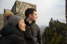 Thoughtful Man And Smiling Asian Woman In Knitted Hat With Pompom Looking Away And Enjoying Amazing Landscape Of Ancient Castle In San Marino, Italy