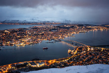 Magnificent Scenery Of City With Golden Lights Located On Island And Shores Of Strait Against Foggy Hills Covered With Snow Under Lush Clouds In Winter Night