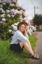 Smiling Ginger Carefree Female Closed Eyes Sitting Among Large Bushes Of Colorful Hydrangeas In Garden In Asturias Looking Away