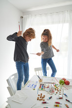 Delighted Boy And Girl In Casual Outfit Looking At Each Other And Crossing Paintbrushes While Standing On Chairs Near Table With Watercolor And Playing At Home