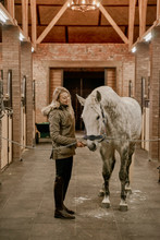 Woman Hugging Horse With Long Mane In Face In Stable