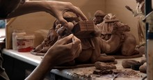 Crop Person Smoothing Statuette Of Decorative Clay Camel On Table In Pottery