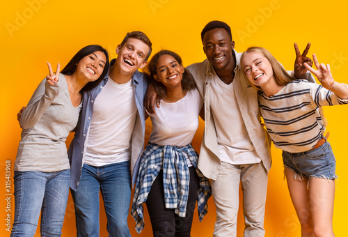 Group of multiracial students smiling and embracing over yellow background