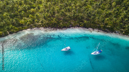 Obraz San Blas Islands, Panama - Aerial Drone Top Down View of two Sailing Yachts anchored in Turquoise Water right next to perfect White Sand Beach of Caribbean Tropical Island full of green Palm Trees. - fototapety do salonu
