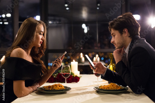 Photo Young man and woman absorbed with mobile phones