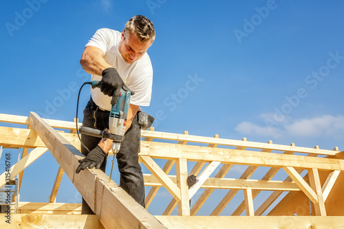 Carpenter at Work, Fixing a Rafter with a Long Screw Fototapete