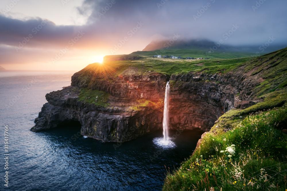 Fototapeta Incredible sunset view of Mulafossur waterfall in Gasadalur village, Vagar Island of the Faroe Islands, Denmark. Landscape photography