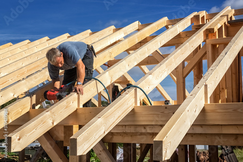 Photographie Carpenters Setting up a Half-timbered Building and the Roof Structure