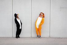 Two Women In Penguin And Lion Costume In Front Of Concrete Wall