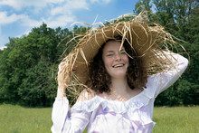 Portrait Of Laughing Young Woman Wearing Frayed Straw Hat In Nature