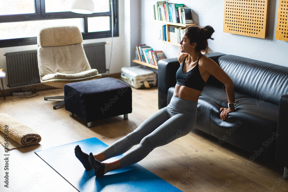 Fototapeta Fitness workout at home. Healthy fit young woman doing triceps dips exercise in the living room.