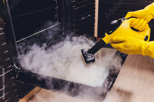 Obraz steam cleaning oven house cleaning hand close-up. - fototapety do salonu