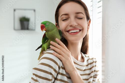 Obraz na płótnie Young woman with cute Alexandrine parakeet indoors