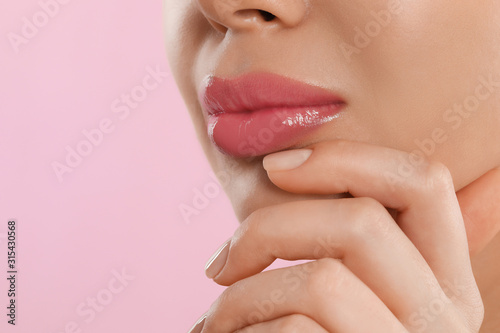 Fotomural  Young woman with beautiful full lips on pink background, closeup