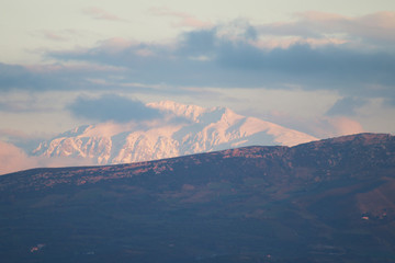 The snow covered Lassithi mountains of Crete in the golden hour. The majestic winter landscape of Crete concept.