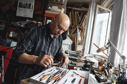 Fotografie, Obraz Man working at typograhpy studio indoors choosing tool pensive
