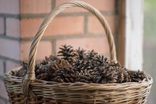 Old Wicker Basket With Pine Cones Near Brick Wall, Closeup.