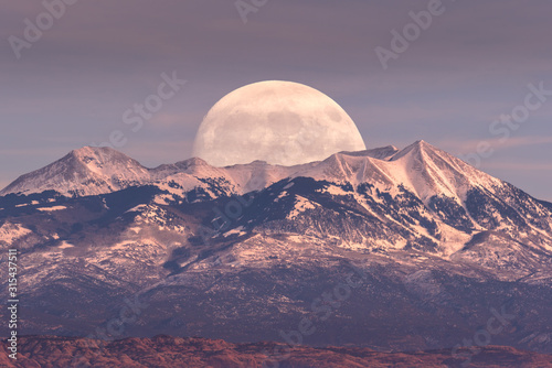 Full moon at it's perigee rising behind La Sal Mountains in Canyonlands National Park during sunset
