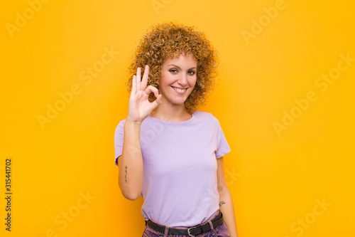young afro woman feeling happy, relaxed and satisfied, showing approval with oka Wallpaper Mural