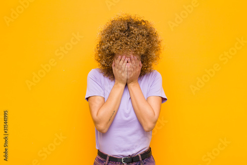 young afro woman feeling sad, frustrated, nervous and depressed, covering face w Canvas Print