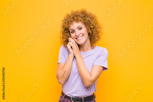 Fotografie, Obraz  young afro woman feeling in love and looking cute, adorable and happy, smiling r