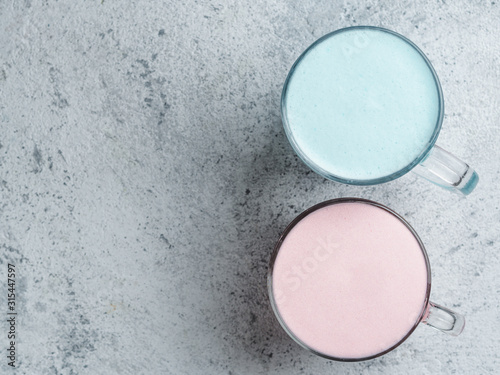 Trendy drink: Blue and pink latte. Top view of hot butterfly pea latte or blue spirulina latte and pink beetroot or raspberry latte on gray cement textured background. Copy space. Top view or flat lay