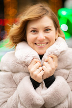 Beautiful Girl In A Light Coat Against The Background Of Multi-colored Lights, Smiling, In Winter, In The New Year Holidays