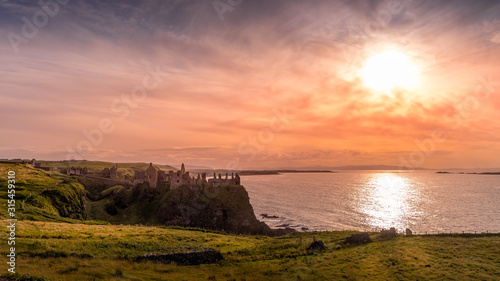 Ruined medieval Dunluce Castle on the cliff at amazing sunset, Wild Atlantic Way, Bushmills, County Antrim, Northern Ireland Wallpaper Mural