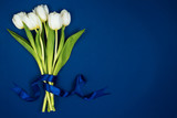 Fototapeta Tulipany - A bouquet of white tulips tied with a ribbon. On a blue background. Postcard for Valentine's Day and March 8th
