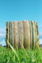 Unique View Of One Hay Bale Taken From Low Angle And Featuring Beautiful Blue Sky And Green Grass, Vertical