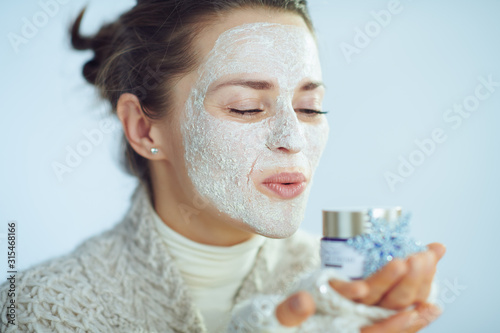 Obraz housewife with facial mask blowing air kiss to cosmetic jar - fototapety do salonu