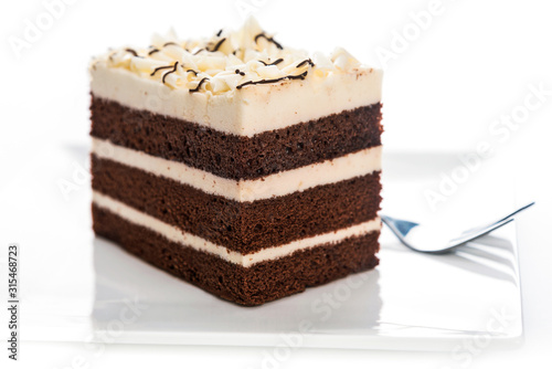 Valokuva Delicious multilayer homemade cocoa sponge cake with sugar mass on a plate with