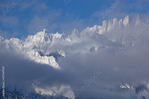 Winter landscape of the Eastern Sierra Nevada Mountains covered in snow and framed by fog and clouds, Lone Pine, California, USA